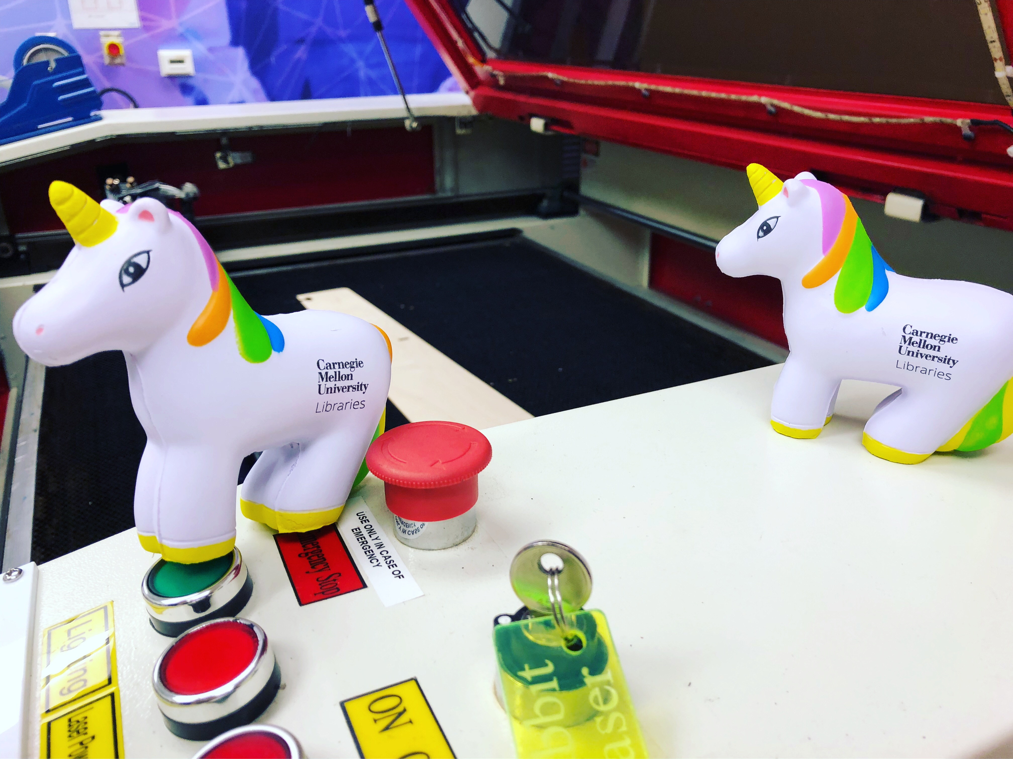 Toy unicorns posed on an IDeATe laser cutter
