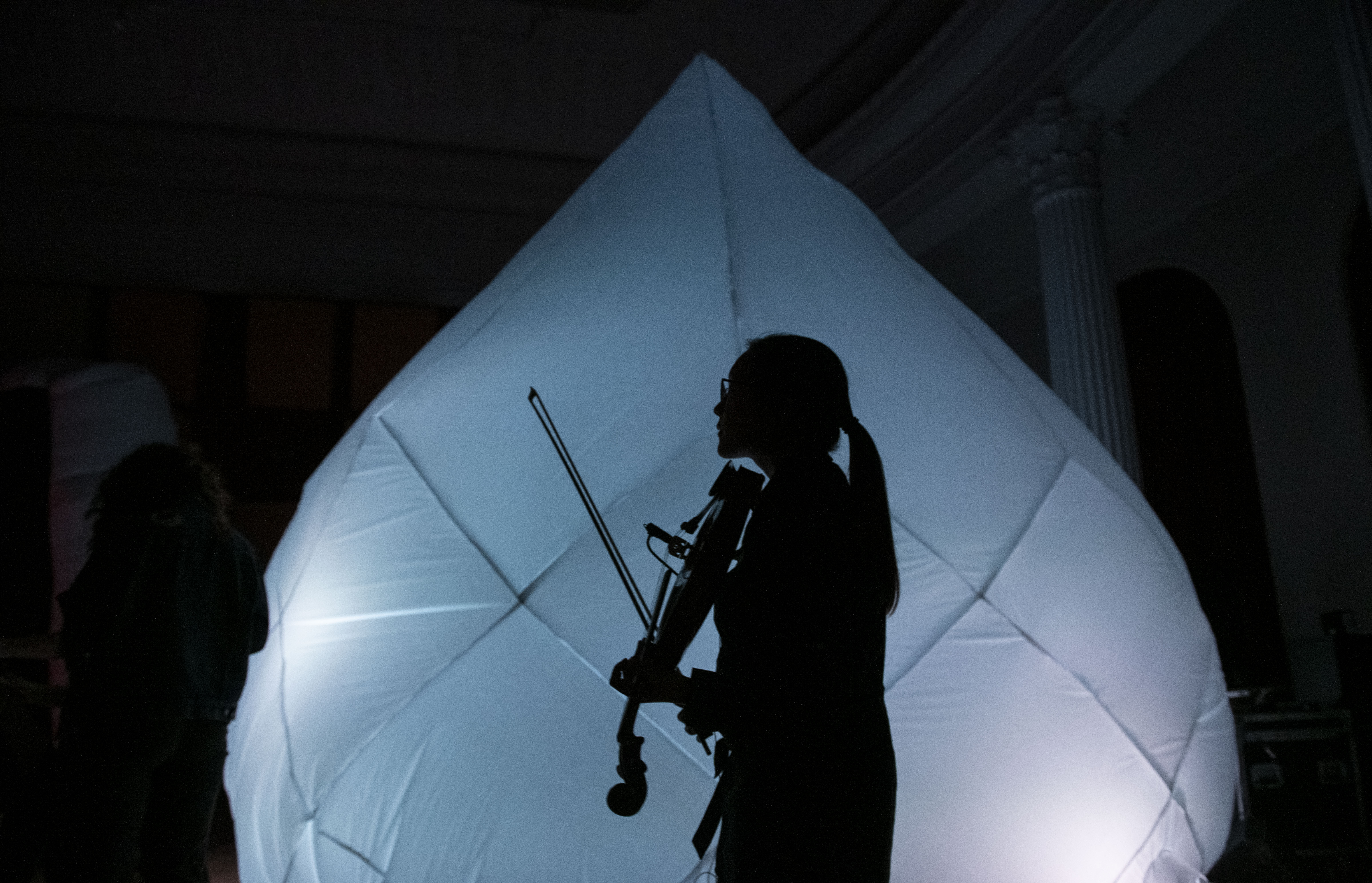 Student playing violin in front of inflatable sculpture