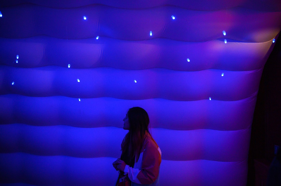 Student in blue-lit inflatable environment looking at twinkle lights above